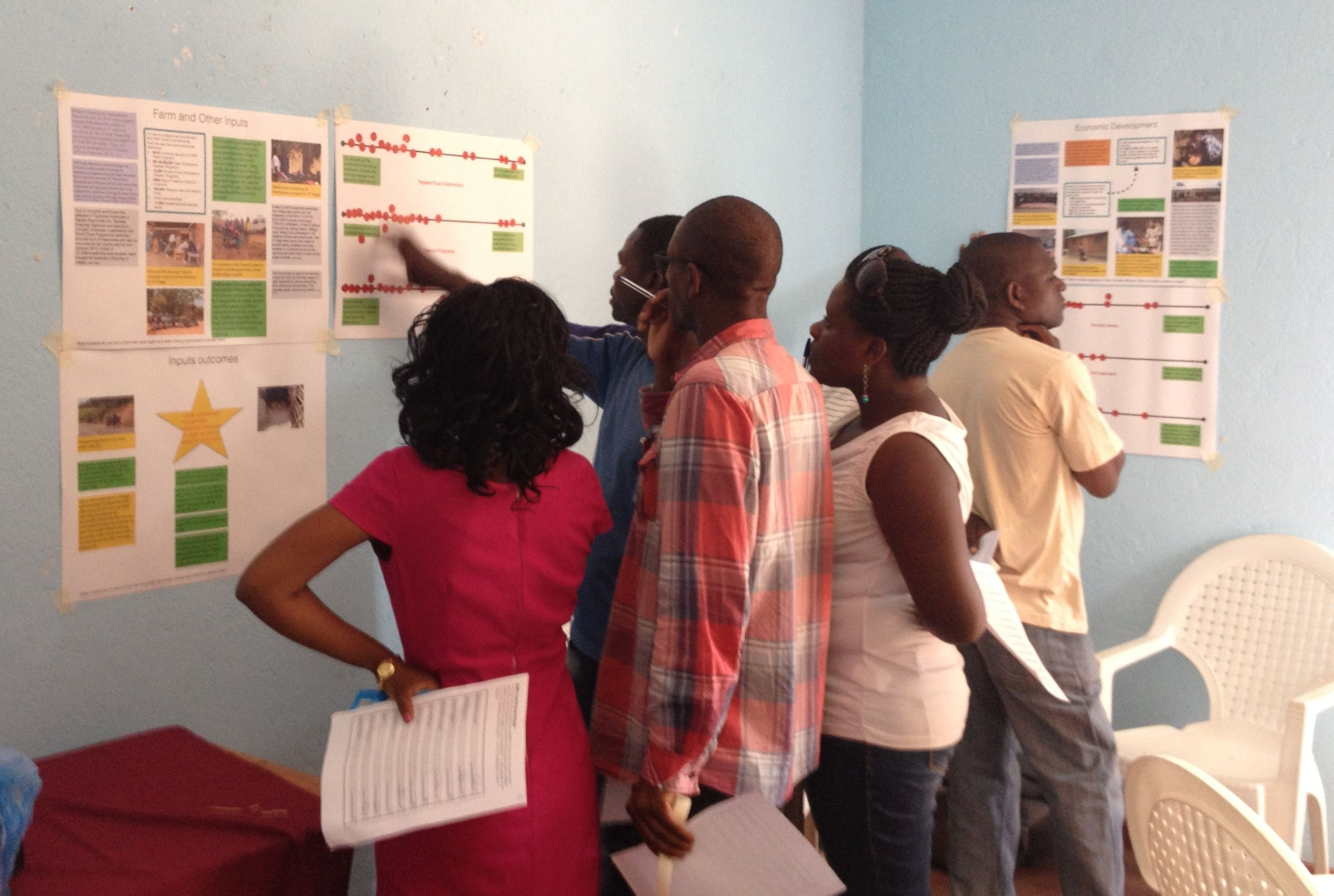 WASH staff look at posters describing activities and outcomes across the whole of CU